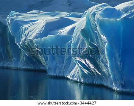 A small part of the sun-reflecting blue front of a larger iceberg. The calm water reflects the beautiful blue ice. Picture was taken during a 3-month Antarctic research expedition near the Peninsula. - stock photo