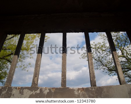 a small piece of sky seen through a barred window, bars in focus - stock photo