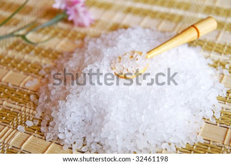 A small pile of coarse sea salt with wooden spoon on a table covered by a bamboo mat, close up, blur background - stock photo