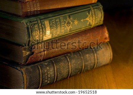 a small pile of old books lit by candle light