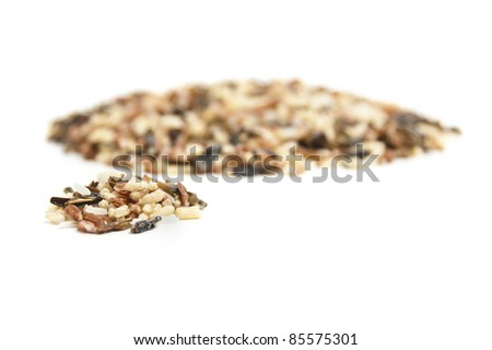 A small pile of wild rice in front of another larger pile. - stock photo