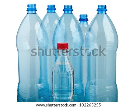 A small plastic bottle with red cap shown in the background of large plastic bottles - stock photo