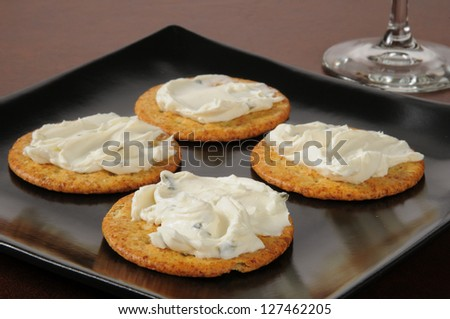 A small plate of crackers topped with chive and green onion cream cheese - stock photo
