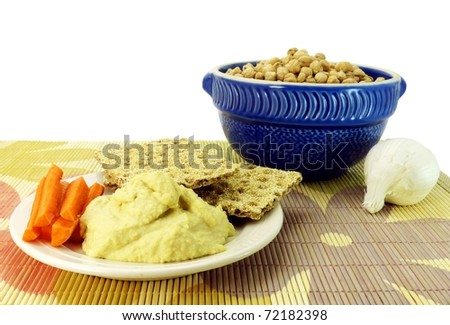 a small plate of healthy organic hummus dip with crackers and carrot sticks on a colorful mat with garlic and a bowl of dried garbanzo beans visible behind it and a pure white background