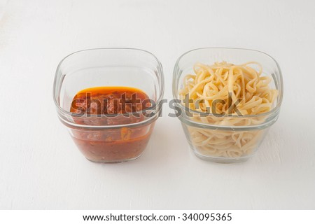 a small portion of plain linguini pasta and tomato sauce in a glass storage containers on white board, image showing a small portion or serving size - stock photo