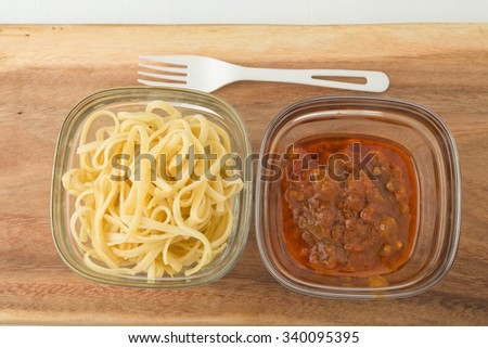 a small portion of plain linguini pasta and tomato sauce in a glass storage containers on wooden chopping board, image showing a small portion or serving size - stock photo
