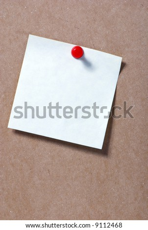 A small post it note on a bulletin board - stock photo