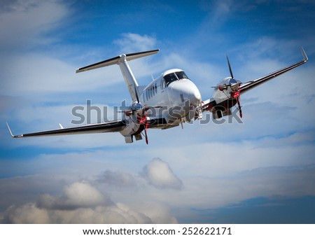 A small private jet in the sky - stock photo