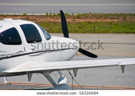 A small private plane tied down next to the runway at a regional airport - stock photo