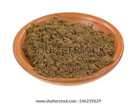 A small red clay bowl filled with ground allspice on a white background.
