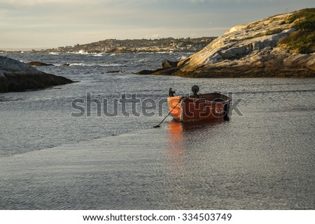 A small red fishing boat rests at anchor in harbor at Peggy's Cove, Nova Scotia, Canada. - stock photo