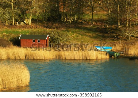 A small red wooden boathouse situated among the reeds near the water. Forest mix with farmers fields in background. As seen in late December from Eriksberg nature reserve in Blekinge, Sweden. - stock photo