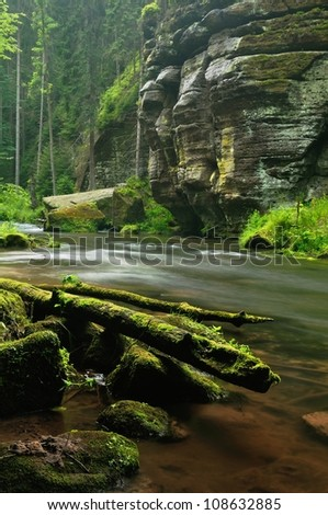 A small river flows through a wild landscape with rocks - stock photo
