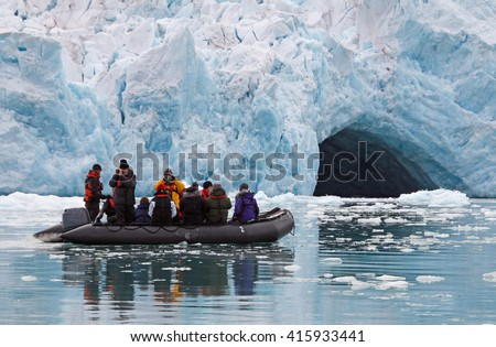 A small rubber dingy in front of a big glacier wall. - stock photo