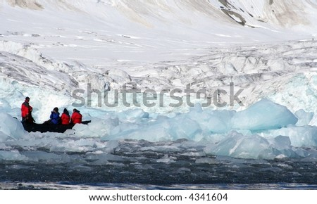 A small rubber dingy sailing through the ice in the arctic