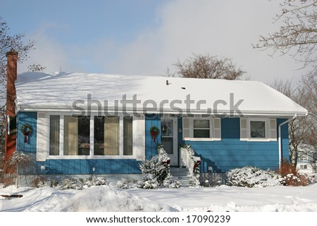 A small 1970's or late 60's bungalow decorated for Christmas and covered in snow. - stock photo