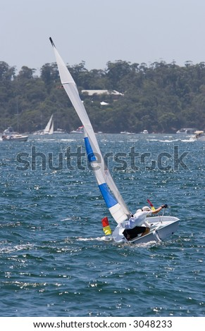 A small sail boat racing on Sydney Harbour - stock photo
