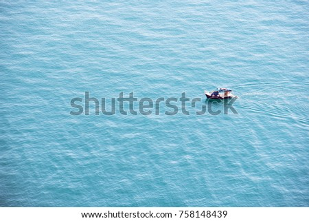 A small sailboat moves along the turquoise sea in a Sunny calm day