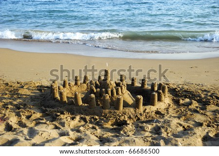 A small sandcastle with a white flag on beach with waves on the background