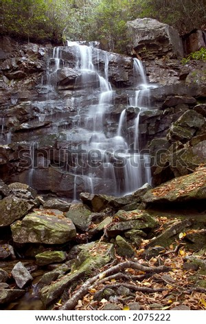 A small secluded waterfall in the forests of West Virginia. I like this type of waterfall with its many ledges for the water to tumble across. - stock photo