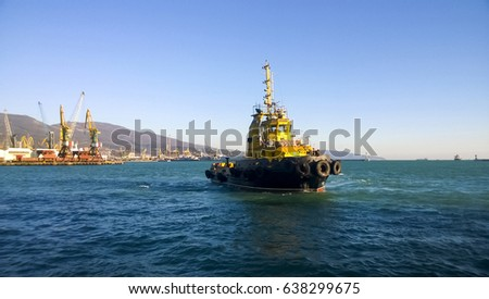 A small service ship in a cargo industrial port. A ship in the sea.