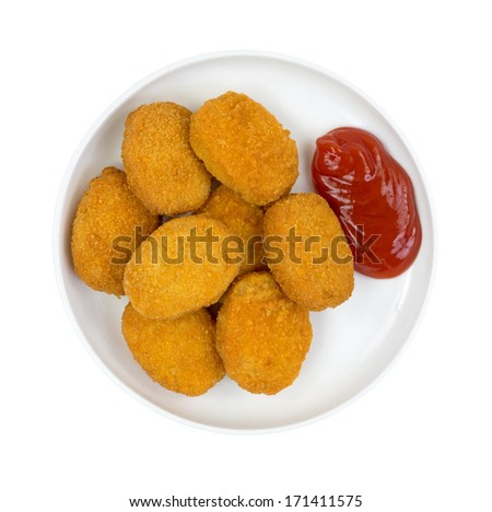 A small serving of cooked breaded chicken pieces with ketchup on a small plate. - stock photo