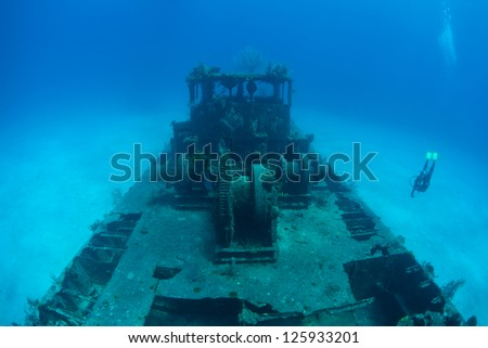 A small shipwreck rests on a sandy sea floor just off the Caribbean island of Grand Cayman.  Cayman is a well known destination for scuba divers and has beautiful coral reefs. - stock photo