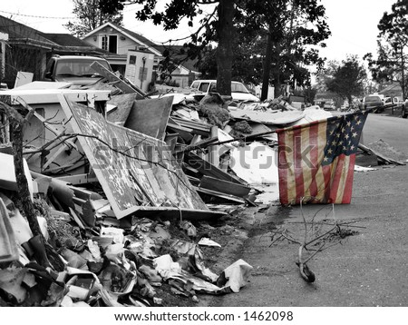 a small sign of hope - a mud-stained and tattered American flag stands in a pile of debris left by Hurricane Katrina in Chalmette, Louisiana - stock photo