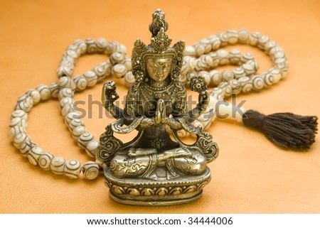 A small silver statue of Buddha Avalokitesvara with bone beads on the background. - stock photo