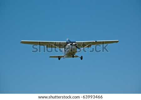 A small single-engined aircraft in flight against a blue sky.