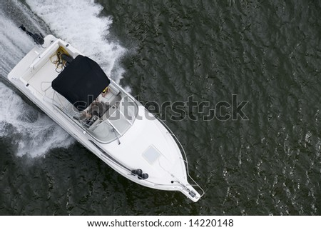 A small speedboat shot from above while travelling fast. - stock photo