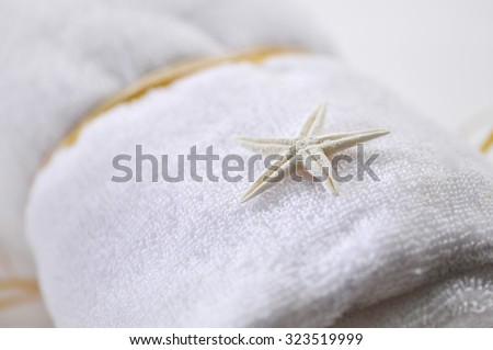 A small star fish seashell placed on rolled white towel - spa object - stock photo