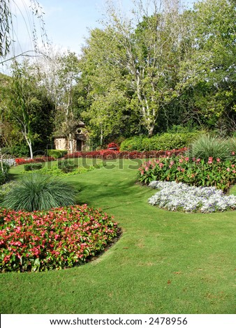 a small stone hut sits in a formal garden - stock photo