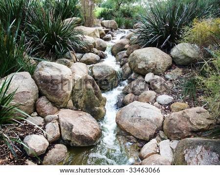 A small stream, flowing through a garden - stock photo