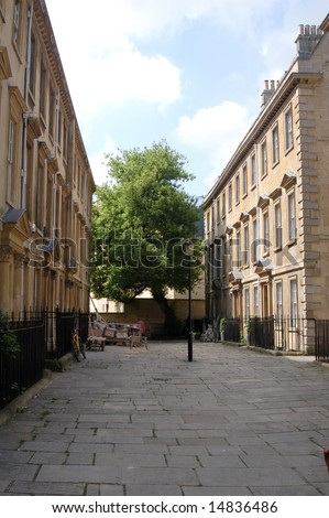 A small street in Bath with pavers and a lamppost