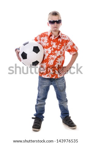A small teenage boy wears an orange shirt and plays with a big football, isolated against white background. - stock photo