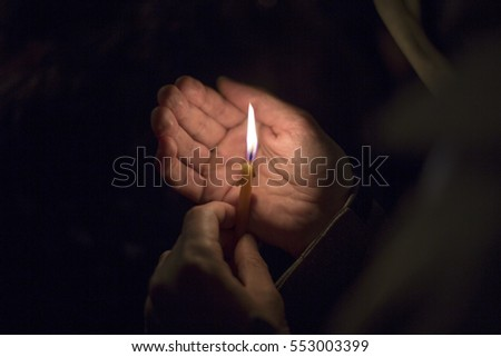 A small tiny burning candle hold with two fingers in front of open palm in the darkness