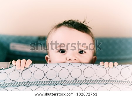 A small toddler boy peers over the top of his crib or playpen with a happy expression.   Processed for an aged vintage retro look.     - stock photo