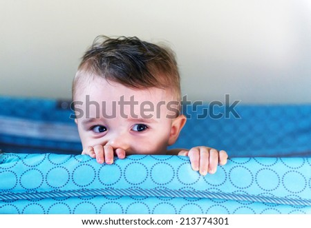 A small toddler boy peers over the top of his crib or playpen with a mischievous look.     - stock photo