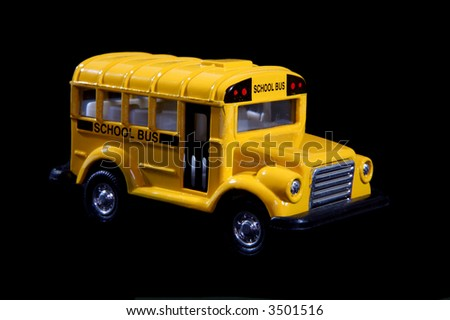 A small toy school bus over black