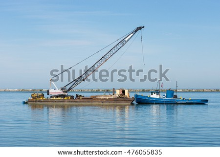 A small tugboat pushes a barge laden with construction materials and a crane westward inside the break wall in the Port of Cleveland, Ohio on Lake Erie