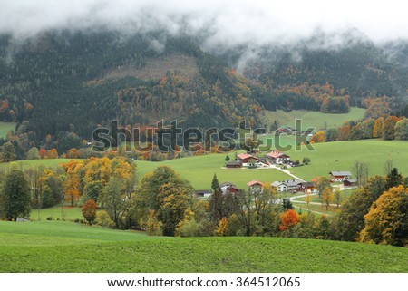 A small village on a beautiful hillside with farmhouses scattered between green meadows and autumn trees ~ Fall scenery of idyllic countryside in Ramsau, Bavaria Germany - stock photo