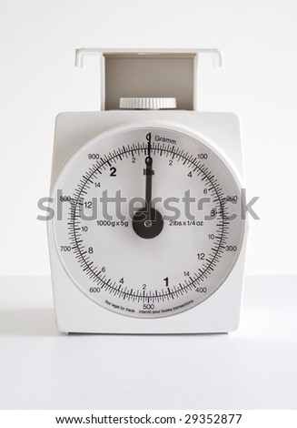 A small, vintage, white kitchen scale for measuring ingredients or letters for calculating postage. - stock photo
