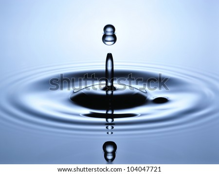 A small water drop fall on water surface and jump back to collide with the second one, forming a calabash shape splash. - stock photo