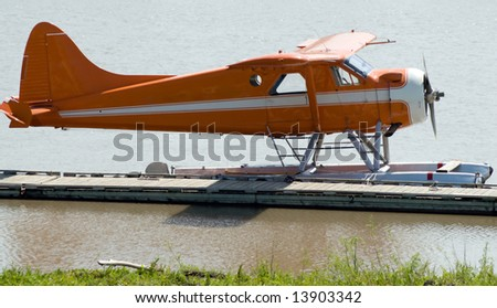 A small water plane docked on the river during the day - stock photo