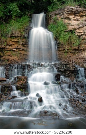 A small waterfall flowing in eastern Kansas. This shot was made with a wide angle lens and a slow shutter speed. - stock photo