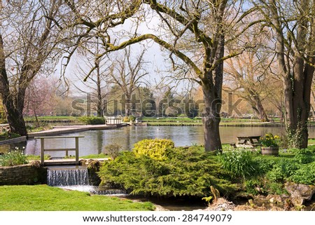 A small waterfall forms on the outflow of a lake surrounded by trees - stock photo