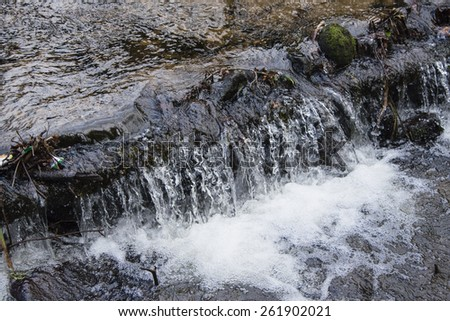 A small waterfall in a woodland stream in England - stock photo