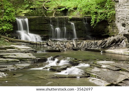 A small waterfall in the forests New Yorks Filmore Glen State Park. The stream is framed with the colorful green leaves and mosses of spring. - stock photo