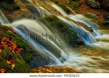 A small waterfall is surrounded by moss and fallen autumn maple leaves, long exposure - stock photo